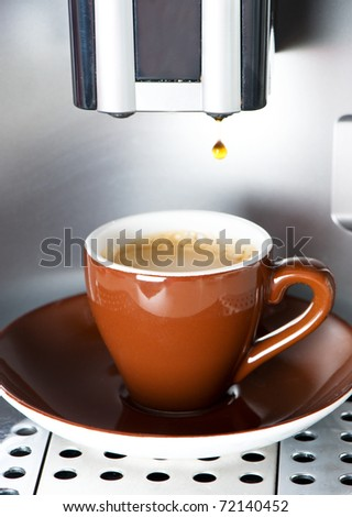 Coffee maker pouring fresh espresso coffee in a cup