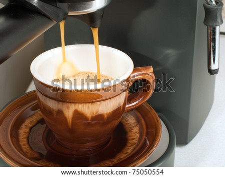 Coffee maker pouring hot espresso coffee in  cups - stock photo