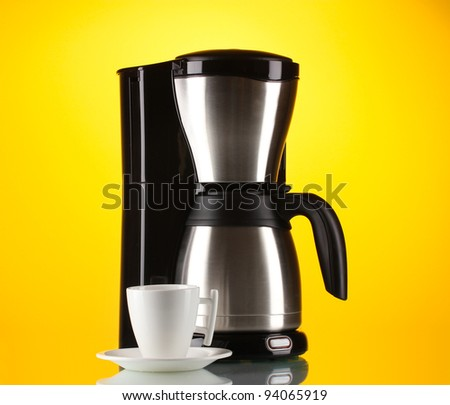Coffee maker with white cup on yellow background
