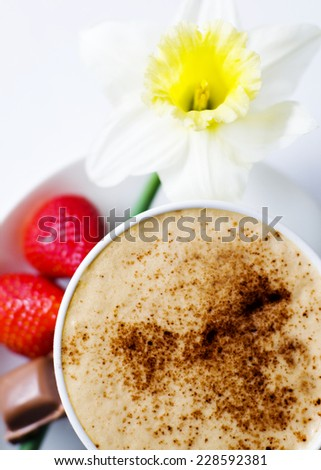 Coffee mocha with strawberries, chocolate and flower as garnish. - stock photo