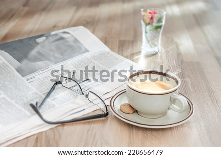Coffee, muffin and financial newspaper in morning light - stock photo
