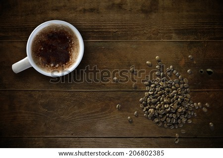 Coffee mug and beans on old rustic table - stock photo