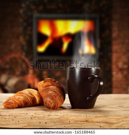 coffee mug and fireplace with croissants