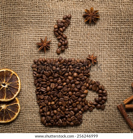Coffee mug made from coffee beans on burlab texture - stock photo
