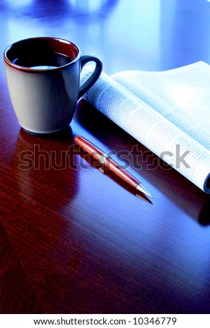 coffee mug magazine and pen on wood desk with blue tone