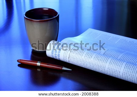 Coffee mug, magazine and pen on wood desk with blue tone