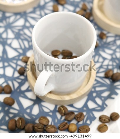 coffee mug on a stand with coffee beans