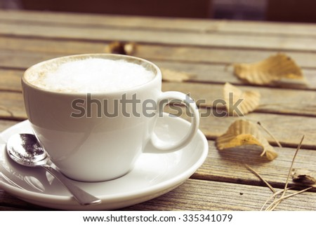 Coffee Mug on a Wooden Table with autumnal colored leaves