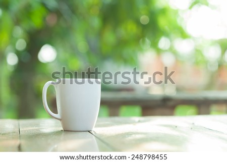 coffee mug on blur green garden background