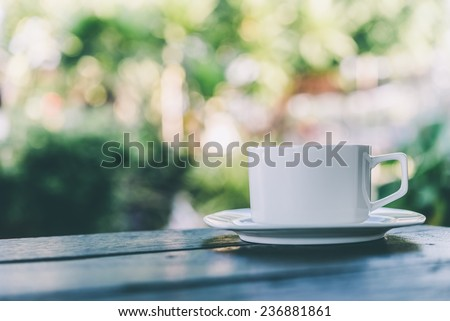 Coffee mug on wooden table outdoor background - Vintage effect style pictures - stock photo