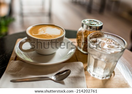 Coffee mug with brown sugar and glass of water set on wooden board. - stock photo