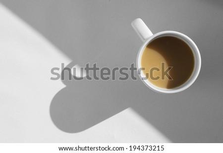 coffee mug with cappuccino on light grey background. Mimimalistic studio shoot. Above view - stock photo