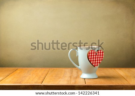 Coffee mug with heart shape on wooden table - stock photo
