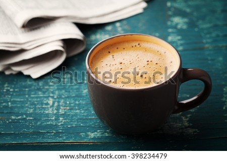 Coffee mug with newspaper on teal rustic table, cozy breakfast, vintage style - stock photo
