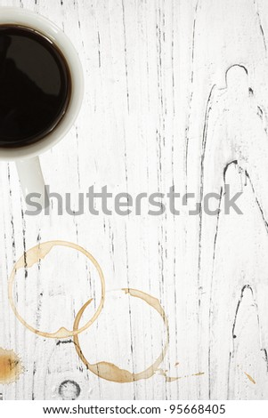 Coffee mug with stains and splashes over grunge white timber background. - stock photo