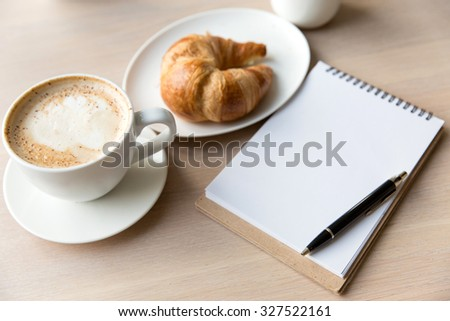 coffee , notebook and croissant on a wooden table - stock photo