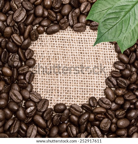 Coffee on burlap background with green leaves. Round space for the text - stock photo