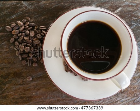 coffee on cup and coffee beans on vintage wood table background