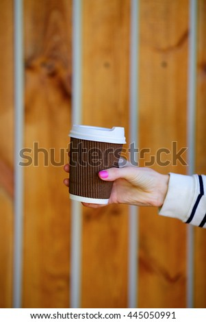 Coffee on the go. Disposable cup in woman hand on background of wooden planks - stock photo