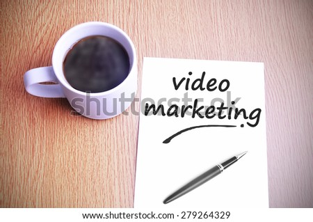 Coffee on the table with note writing video marketing. - stock photo