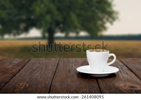 Coffee on wooden table with beautiful autumn field background - stock photo