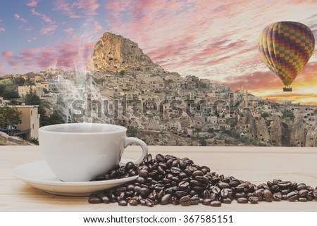 Coffee on wooden table with Hot air balloons flying over cappadocia. - stock photo