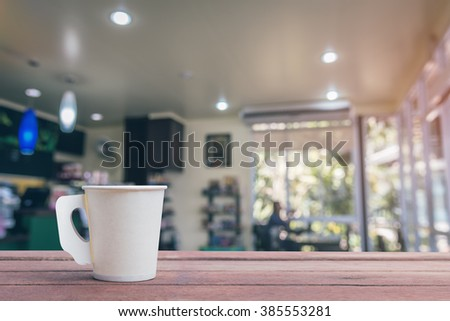 Coffee paper cup in coffee shop blur background - stock photo