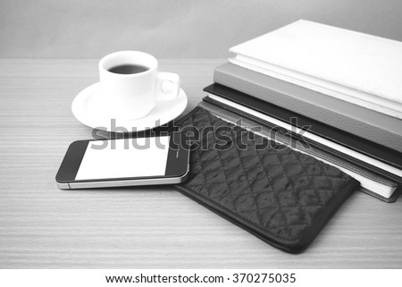 coffee,phone,stack of book and wallet on wood table background black and white color