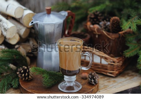 Coffee pot and a cup of coffee on the table with Christmas decorations