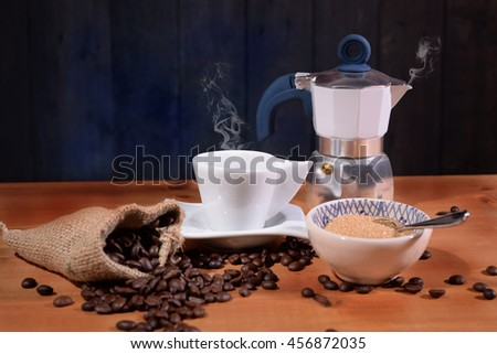 Coffee pot and cup with aromatic coffee and sugar cane