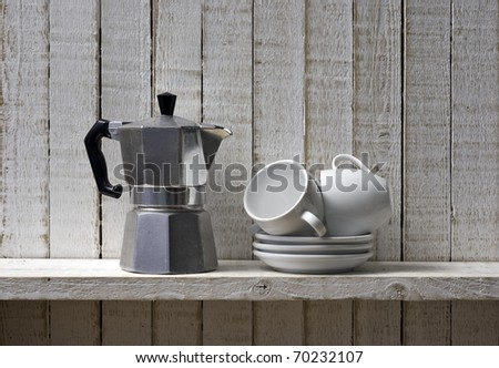 Coffee pot and pile of coffee cups on shelf