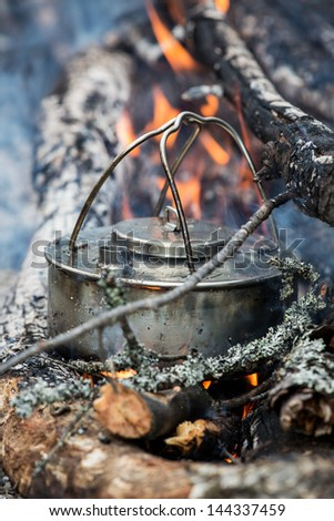 Coffee pot in camp fire. Making coffee outside. - stock photo