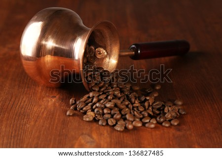 Coffee pot with coffee beans on brown wooden background
