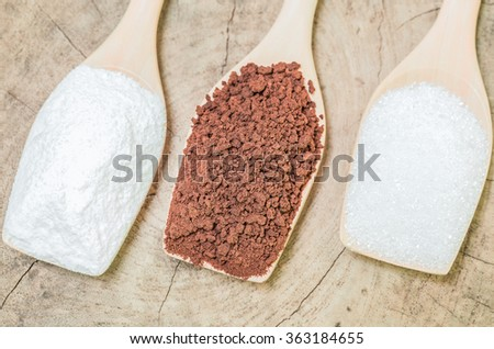 Coffee powder and creamer with sugar cubes on wooden spoon - stock photo