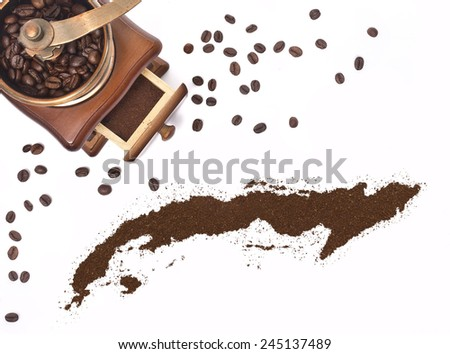Coffee powder in the shape of Cuba and a decorative coffee mill.(series) - stock photo
