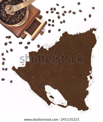 Coffee powder in the shape of Nicaragua and a decorative coffee mill.(series) - stock photo