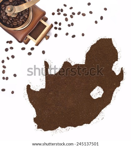 Coffee powder in the shape of South Africa and a decorative coffee mill.(series) - stock photo