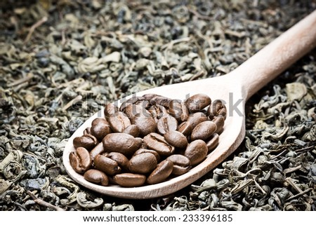 Coffee seeds, green tea leafs and wooden spoon. - stock photo