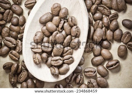 Coffee seeds on wooden spoon.