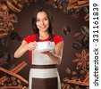 Coffee serving waitress. Young asian barista woman smiling showing cup of coffee. Isolated on brown background. Focus on waitress. - stock photo