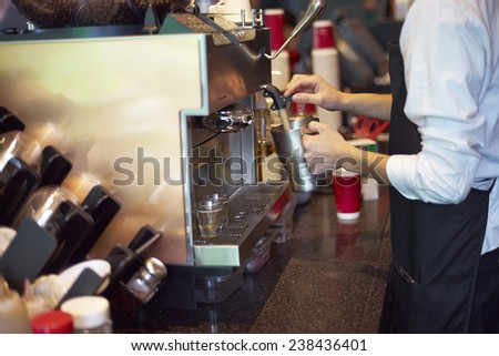 coffee shop staff steaming milk - stock photo