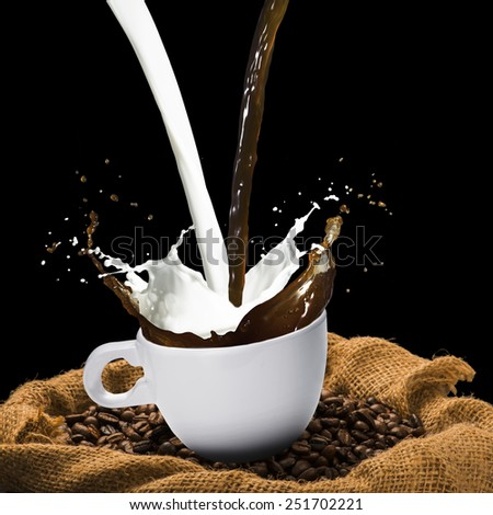 Coffee Splash From Cup on Coffee Beans - stock photo