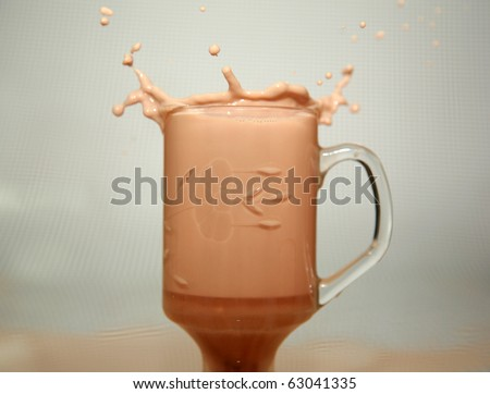coffee splashing as someone drops a sugar cube into it from a distance on a black and white background - stock photo
