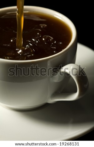 coffee splashing into white cup isolated - stock photo