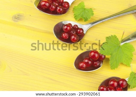 Coffee spoon with red currants on a yellow wooden table. Preparing for home baking currant dessert. - stock photo