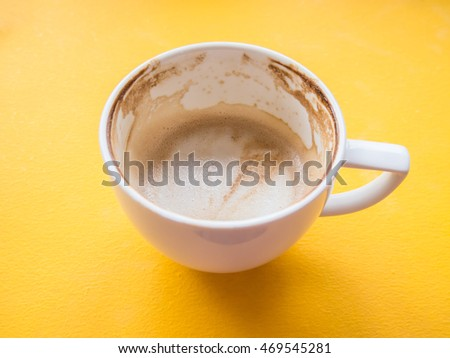 Coffee stains on empty mug on a yellow table in a coffee shop