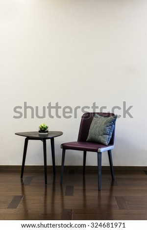 Coffee table Leather chair combination in front of a plain wall - stock photo