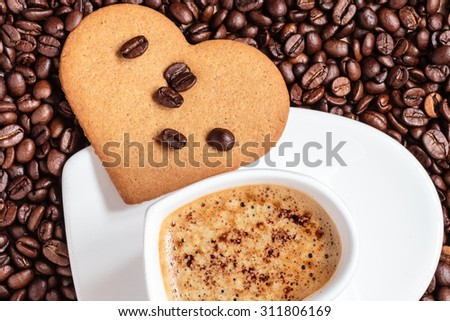 Coffee time concept. Heart shaped cup with cappuccino mocha and cookie gingerbread on coffee beans background. Top view - stock photo