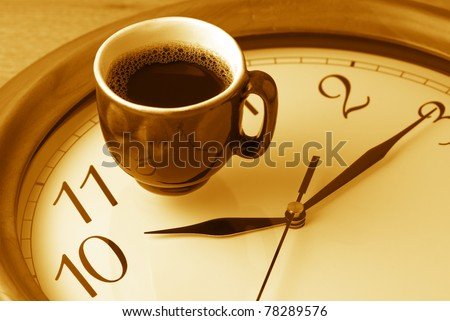 Coffee time: cup of coffee on clock dial. Monochrome toned image. - stock photo