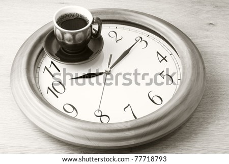 Coffee time: cup of coffee on clock dial. Sepia. - stock photo